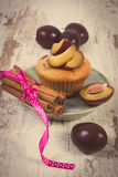 Vintage photo, Fresh baked muffins with plums and cinnamon sticks on old wooden background, delicious dessert Royalty Free Stock Image