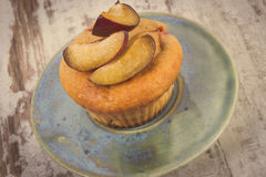 Vintage photo, Fresh baked muffins with plums on plate on old wooden background, delicious dessert Stock Image