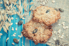 Vintage photo, Fresh baked oatmeal cookies and ears of oat, healthy dessert concept Royalty Free Stock Images