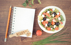 Vintage photo, Fresh greek salad with vegetables and notepad for writing notes, healthy nutrition. Vintage photo, Fresh greek salad with vegetables and notepad Stock Photo