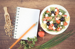 Vintage photo, Fresh greek salad with vegetables and notepad for writing notes. Concept of healthy nutrition, lifestyle and slimming Stock Image