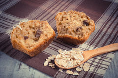 Vintage photo, Fresh muffin with oatmeal baked with wholemeal flour on checkered tablecloth, delicious healthy dessert Stock Photo