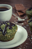 Vintage photo, Fresh muffin with spinach, desiccated coconut, chocolate glaze and cup of coffee, delicious healthy dessert Royalty Free Stock Photo