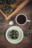 Vintage photo, Fresh muffins with spinach, desiccated coconut, chocolate glaze and cup of coffee, delicious healthy dessert Stock Images