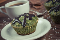 Vintage photo, Fresh muffins with spinach, desiccated coconut, chocolate glaze and cup of coffee, delicious healthy dessert Royalty Free Stock Photography