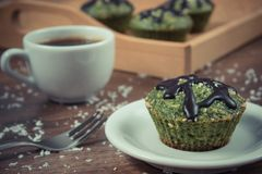 Vintage photo, Fresh muffins with spinach, desiccated coconut, chocolate glaze and cup of coffee Stock Photos