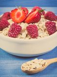 Vintage photo, Fresh oat flakes or oatmeal with strawberries and raspberries, healthy lifestyle and nutrition. Vintage photo, Fresh prepared oat flakes or Stock Photos