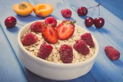 Vintage photo, Oat flakes and oatmeal with fruits, healthy lifestyle and nutrition. Vintage photo, Fresh prepared oat flakes and oatmeal with fruits, concept of Royalty Free Stock Photo