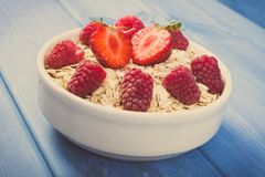 Vintage photo, Fresh oat flakes or oatmeal with strawberries and raspberries, healthy lifestyle and nutrition. Vintage photo, Fresh prepared oat flakes or Royalty Free Stock Photography