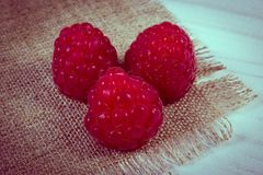 Vintage photo, Fresh raspberries on canvas and wooden table, healthy food Stock Photography