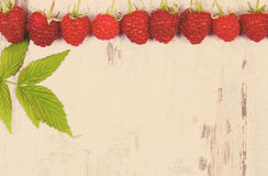 Vintage photo, Fresh raspberries with leaf and copy space for text on old wooden background Royalty Free Stock Image