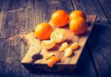 Vintage photo of fresh tangerines on wooden cutting board Royalty Free Stock Photo