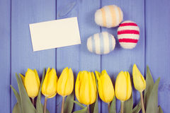 Vintage photo, Fresh tulips and Easter eggs wrapped woolen string, copy space for text on sheet of paper Royalty Free Stock Images