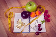 Vintage photo, Fruits, tablets supplements and centimeter with notebook, slimming and healthy food Stock Photos