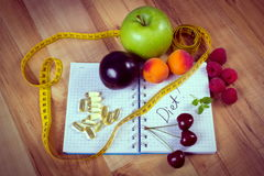 Vintage photo, Fruits, tablets supplements and centimeter with notebook, slimming and healthy food Stock Photography