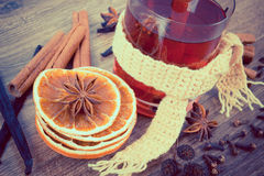 Vintage photo, Glass of mulled wine wrapped scarf with fresh fragrant spices Stock Images