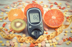 Vintage photo, Glucometer with result, centimeter, fruits and medical pills, diabetes, slimming, healthy lifestyle and nutrition Stock Photos