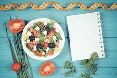 Vintage photo, Greek salad with vegetables, centimeter and notepad for notes, concept of nutrition and slimming. Vintage photo, Greek salad with vegetables, tape Stock Photo