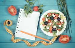 Vintage photo, Greek salad with vegetables, centimeter and notepad for notes, healthy food and slimming concept Stock Photos