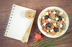 Vintage photo, greek salad with vegetables, centimeter and notepad for notes, healthy nutrition and slimming concept Stock Photography