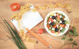 Vintage photo, greek salad with vegetables, centimeter and notepad for notes, healthy nutrition and slimming concept. Vintage photo, Fresh greek salad with Stock Photos