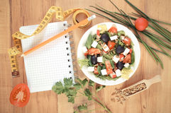 Vintage photo, greek salad with vegetables, centimeter and notepad for notes, healthy nutrition and slimming concept. Vintage photo, Fresh greek salad with Stock Photo