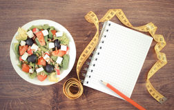 Vintage photo, greek salad with vegetables, centimeter and notepad for notes, healthy nutrition and slimming concept. Vintage photo, Fresh greek salad with Stock Images
