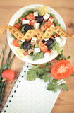 Vintage photo, greek salad with vegetables, centimeter and notepad for notes, healthy nutrition and slimming concept. Vintage photo, Fresh greek salad with Royalty Free Stock Photos