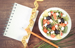 Vintage photo, greek salad with vegetables, centimeter and notepad for notes, healthy nutrition and slimming concept. Vintage photo, Fresh greek salad with Royalty Free Stock Images
