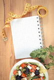 Vintage photo, greek salad with vegetables, centimeter and notepad for notes, healthy nutrition and slimming concept. Vintage photo, Fresh greek salad with Royalty Free Stock Image