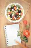Vintage photo, greek salad with vegetables and notepad for notes, healthy nutrition Royalty Free Stock Photos