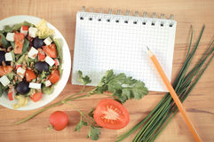 Vintage photo, greek salad with vegetables and notepad for notes, healthy nutrition. Vintage photo, Fresh greek salad with vegetables and notepad for writing Royalty Free Stock Image