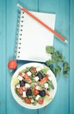 Vintage photo, greek salad with vegetables and notepad for notes. Vintage photo, Fresh greek salad with vegetables and notepad for writing notes, concept of Stock Images