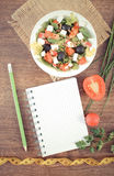 Vintage photo, greek salad with vegetables, tape measure and notepad for notes, healthy nutrition and slimming concept. Vintage photo, Fresh prepared greek salad Royalty Free Stock Image
