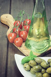 Vintage photo of green olive salad, tomatoes and oil bottle Royalty Free Stock Photos