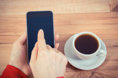 Vintage photo, Hand of woman touching blank screen of mobile phone, cup of coffee Stock Photos