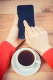 Vintage photo, Hand of woman touching blank screen of mobile phone, cup of coffee Royalty Free Stock Images