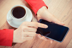 Vintage photo, Hand of woman touching screen of mobile phone or smartphone, cup of coffee Stock Image