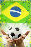 Vintage photo of hands holding soccer ball and Brazil flag Royalty Free Stock Image