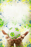 Vintage photo of hands holding soccer ball and Brazil flag Stock Photography