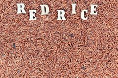 Vintage photo, Heap of red rice with inscription as background, healthy gluten free food concept Stock Photography