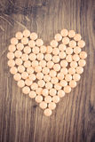 Vintage photo, Heart shaped medical pills and capsules, health care concept. Vintage photo, Heart shaped medical pills, capsules or supplements for therapy royalty free stock photography