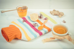 Vintage photo, Hot water bottle, cup of tea and ingredients for preparation warming beverage Stock Photos