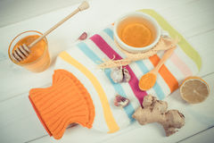 Vintage photo, Hot water bottle, cup of tea and ingredients for preparation warming beverage Royalty Free Stock Photo