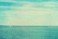 Vintage photo of lighthouse tower. Nautical texture background. Stock Photos