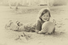 Vintage photo of little beautiful girl playing in the park. retro old style filtered image Stock Photo