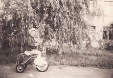 Vintage photo of little girl on old bicycle Royalty Free Stock Image
