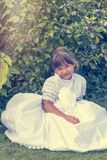 Vintage photo of little girl sitting in white bridesmaid clothes royalty free stock image