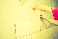 Vintage photo of man hands work with tiles and mortar Stock Photography