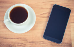 Vintage photo, Mobile phone with blank screen and cup of coffee Stock Photos
